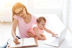 有工作和使用智能手机的婴孩的母亲 免版税图库摄影