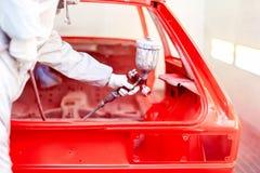 有工作在一辆红色汽车的工作者的喷漆枪特写镜头  免版税库存照片