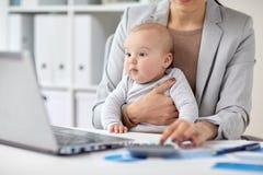 有工作在办公室的婴孩的女实业家 免版税库存图片