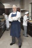 有工作在厨房里的同事的确信的男性厨师 库存照片