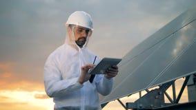 有工作在它旁边的一位男性能学工程师的太阳建筑 股票视频