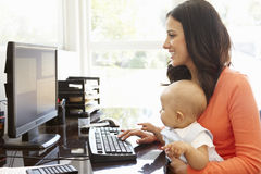 有工作在家庭办公室的婴孩的西班牙母亲 免版税图库摄影