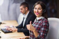 年轻有工作在背景中的同事的电话中心操作员佩带的耳机画象在办公室 免版税库存照片