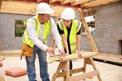 有工作在建筑工地的女性学徒的木匠 免版税库存照片