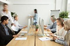 有工作在comp的不同的人民的繁忙的现代coworking的办公室 免版税库存照片