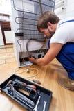 有工具的安装工在厨房里 免版税库存照片