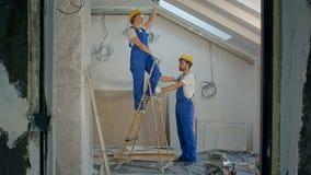 有工具的建筑工人佩带的工作者更新公寓的 股票录像