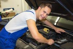 有工具的技工在修理汽车的马达的车库 免版税库存图片