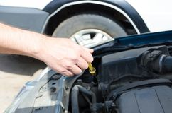 有工具的检查油面的汽车机械师的手 免版税库存照片