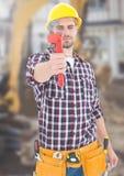 有工具的建筑工人在建造场所前面 免版税库存照片