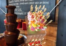 有巧克力喷泉涮制菜肴塔的五颜六色的果冻棍子点心的 免版税库存图片