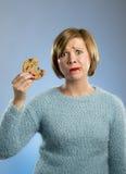 有巧克力污点的逗人喜爱的美丽的妇女在嘴吃大可口曲奇饼的 库存照片