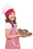 有巧克力油炸圈饼的小女孩厨师 免版税库存图片