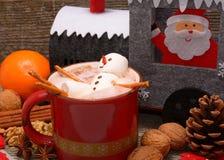 有巧克力热饮和圣诞装饰的红色杯子 免版税库存照片
