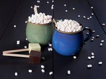 有巧克力热饮和微型蛋白软糖的两个杯子,在黑褐色背景 免版税库存照片