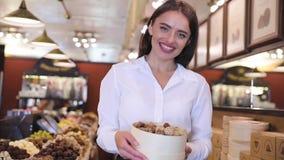 有巧克力甜点的商店 在陈列室附近的微笑的女推销员 股票录像