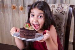 有巧克力蛋糕的年轻小美丽的中东儿童女孩用菠萝、草莓和牛奶与红色礼服和黑暗的e 库存图片