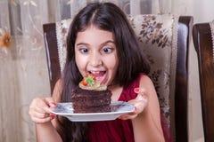 有巧克力蛋糕的年轻小美丽的中东儿童女孩用菠萝、草莓和牛奶与红色礼服和黑暗的e 免版税库存图片