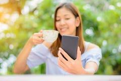 有巧妙的电话的一名被弄脏的美丽的亚裔长的头发妇女和 免版税库存图片