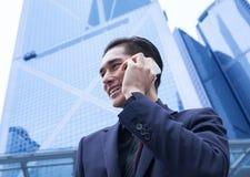 有巧妙的电话的亚裔商人 免版税库存图片