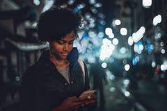 有巧妙的电话的卷曲两种人种的女孩在夜城市街道上 免版税库存图片