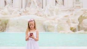 有巧妙的电话的可爱的小女孩户外温暖的天在著名Fontana di Trevi附近的欧洲城市 股票视频