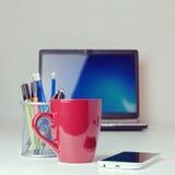 有巧妙的电话的咖啡杯在办公桌上 免版税库存图片