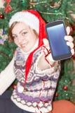 有巧妙的电话的女孩在圣诞树背景 免版税库存图片