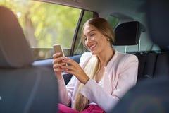 有巧妙的电话的妇女在汽车 免版税库存图片
