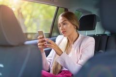 有巧妙的电话的妇女在汽车 免版税库存照片