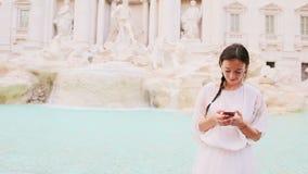 有巧妙的电话的少妇户外温暖的天在著名Fontana di Trevi附近的欧洲城市 股票视频