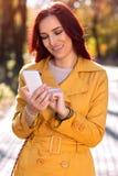 有巧妙的电话的愉快的秋天秀丽妇女 图库摄影