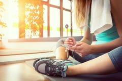 有巧妙的电话的白肤金发的妇女,休息在健身房锻炼以后 库存图片
