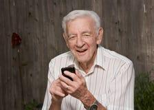 有巧妙的电话的老人 免版税库存照片