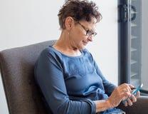 有巧妙的电话的老妇人 免版税库存照片