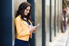 有巧妙的电话的年轻深色的妇女在都市背景中 库存照片