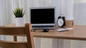 有巧妙的电话笔记本和咖啡杯的膝上型计算机在工作场所桌上 库存照片