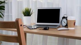 有巧妙的电话笔记本和咖啡杯的膝上型计算机在工作场所桌上 库存图片