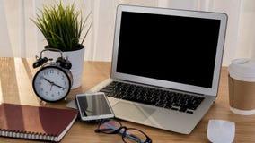 有巧妙的电话笔记本和咖啡杯的膝上型计算机在工作场所桌上 免版税库存照片