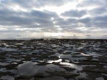 有巨人积雨云的岩石月球风景海在天际的天空和货船 意大利托斯卡纳 库存图片