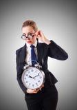 有巨型闹钟的书呆子女实业家 免版税图库摄影