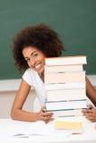 有巨大的堆的微笑的年轻老师书 免版税图库摄影
