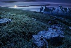 有巨大的石头的草甸在山脉顶部在晚上 图库摄影