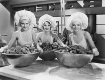 有巨大的碗的三名妇女油炸圈饼 免版税库存图片