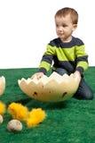 有巨大的蛋形状和玩具小鸡的小的男孩 免版税库存图片
