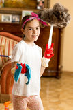 有布料和羽毛刷子的青少年的女孩清洁客厅 图库摄影
