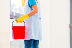 有布料的清洁女工在窗口 免版税图库摄影