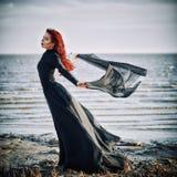有布料的美丽的哀伤的goth女孩在站立在海岸的手上 免版税库存图片