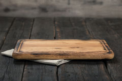 有布料餐巾的空的切板在木桌上 免版税图库摄影