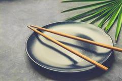有布朗竹筷子棕榈树叶子的黑空的板材在深灰具体石背景 亚洲泰国中国烹调 库存照片